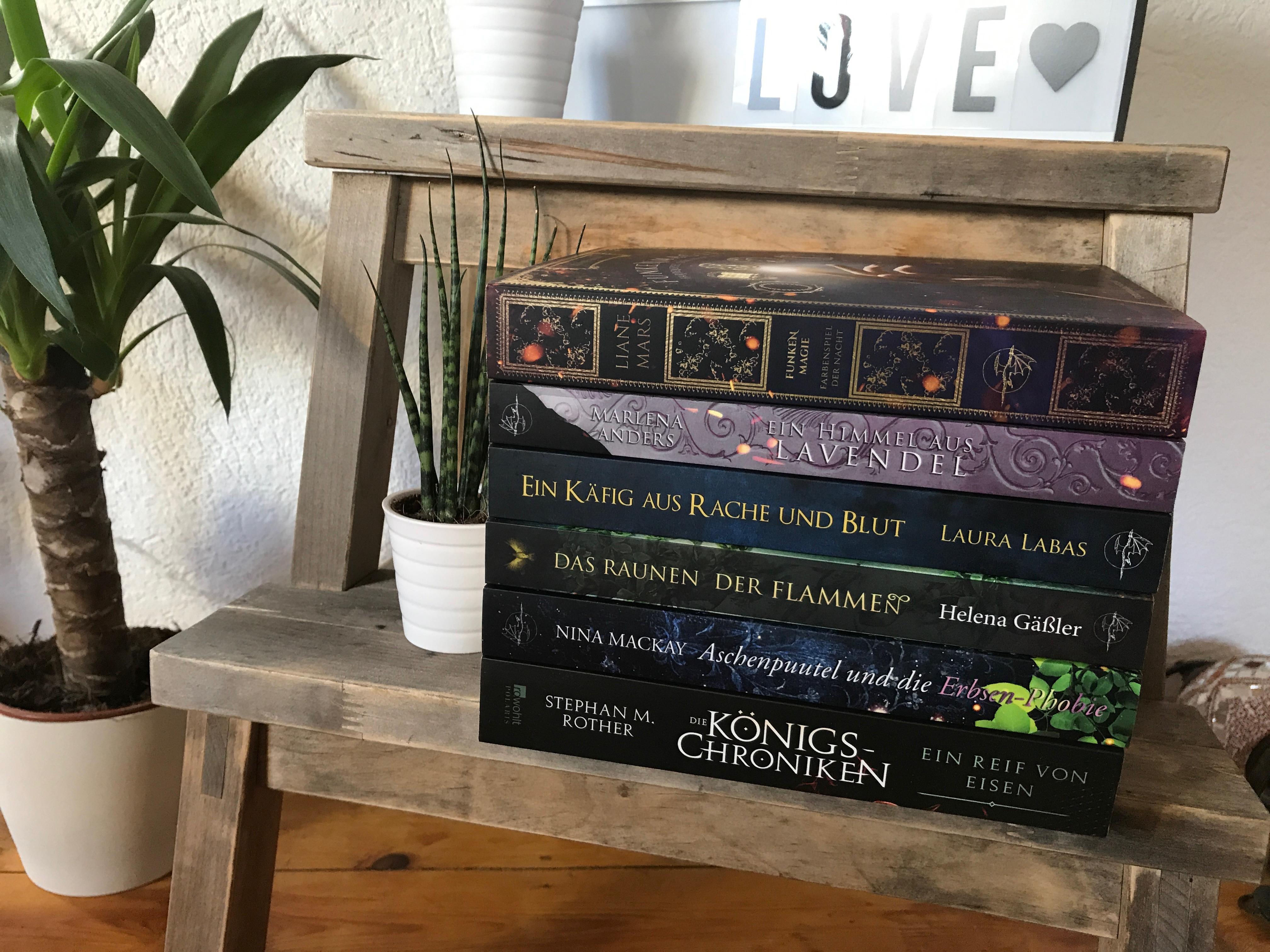 Bücherstapel auf Hocker neben zwei Pflanzen