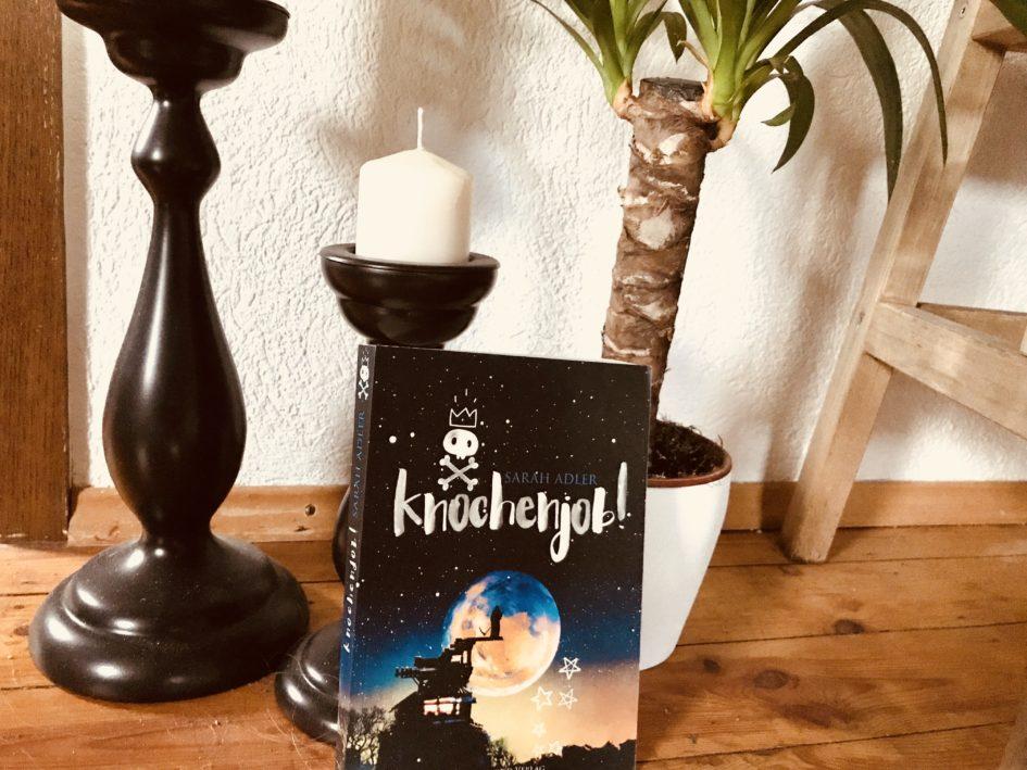 Buchcover vor Pflanze und Kerzen